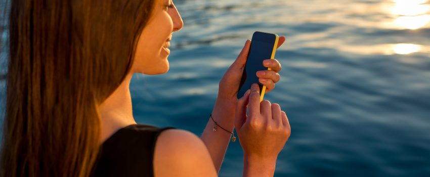Young woman using phone at sunrise
